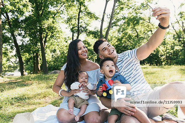 Parents with baby and toddler sons taking smartphone selfie in Pelham Bay Park  Bronx  New York  USA