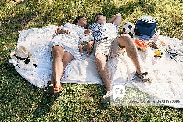 Baby boy lying between parents on picnic blanket in Pelham Bay Park  Bronx  New York  USA