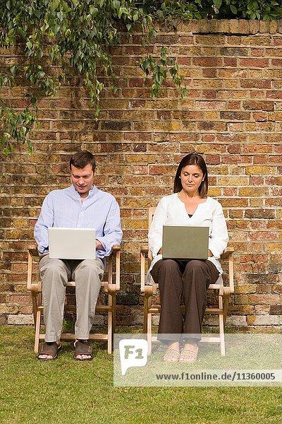Reife Paare sitzen im Garten mit Laptops