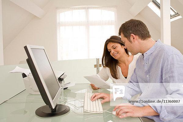Reife Paare  die Rechnungen und Papierkram auf dem heimischen Desktop-Computer prüfen.