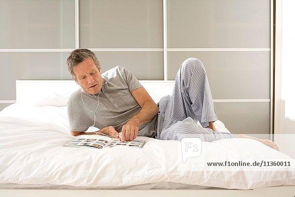Senior Mann liegt auf dem Bett  liest Magazin und hört Kopfhörer.