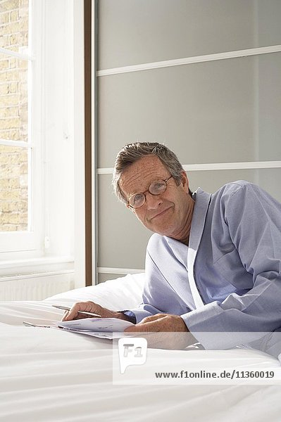 Porträt eines älteren Mannes  der auf dem Bett liegt und Papierkram erledigt.