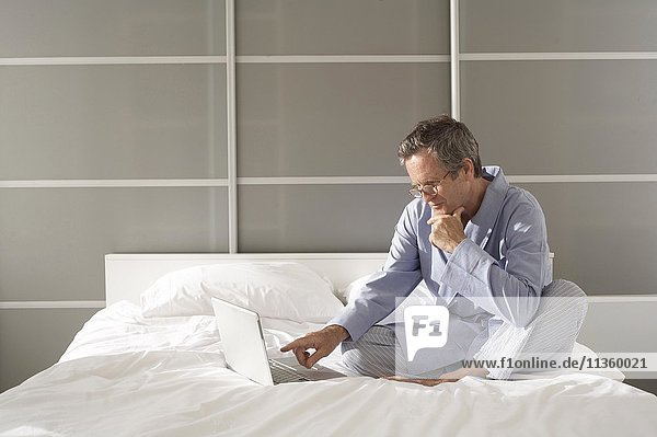 Verwirrter älterer Mann auf dem Bett  der auf den Laptop zeigt.