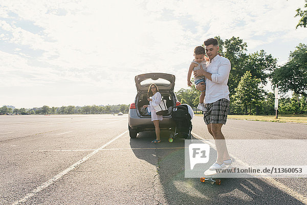 Young man carrying toddler son whilst skateboarding  Pelham Bay Park  Bronx  New York  USA