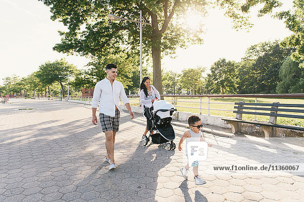 Parents walking with pushchair and toddler son at Pelham Bay Park  Bronx  New York  USA