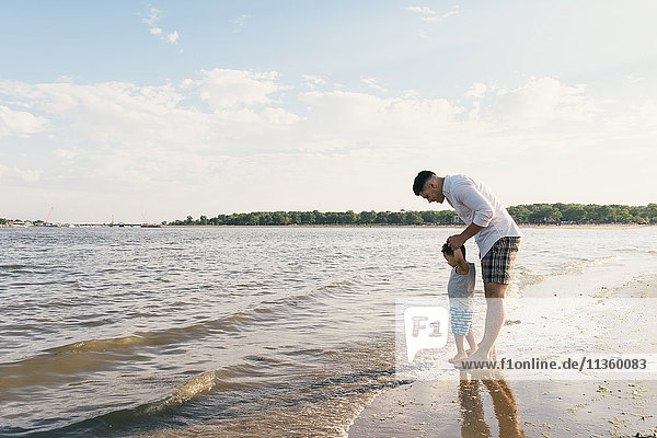 Young man with toddler son looking down at sea  Pelham Bay Park  Bronx  New York  USA