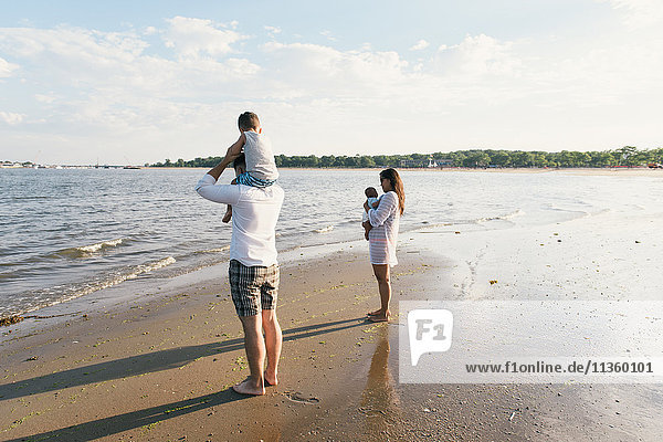 Parents with toddler son and baby boy on beach at Pelham Bay Park  Bronx  New York  USA