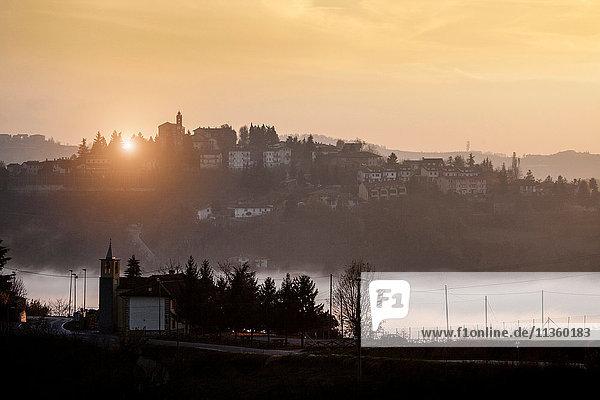 Silhouettierte Landschaft mit Talnebel bei Sonnenuntergang  Langhe  Piemont. Italien