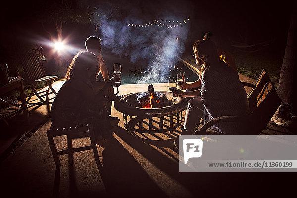 Vier reife Erwachsene sitzen nachts zusammen um das Terrassenfeuer