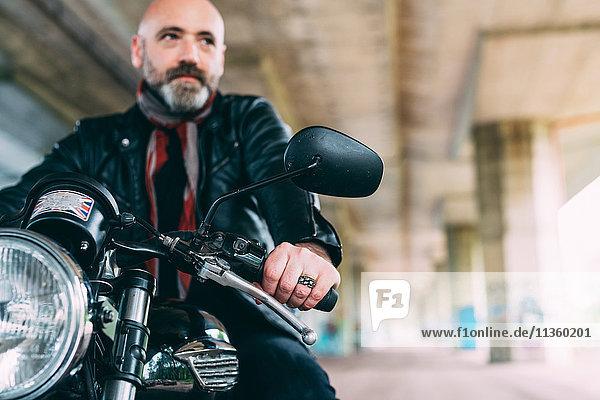 Erwachsener Motorradfahrer auf dem Motorrad sitzend unter der Überführung