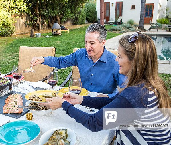 Reife Paare servieren Essen am Gartentisch