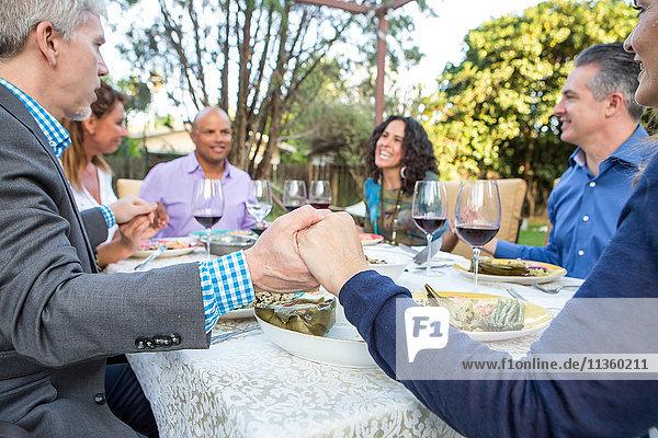 Sechs reife erwachsene Freunde halten sich am Gartenparty-Tisch an den Händen