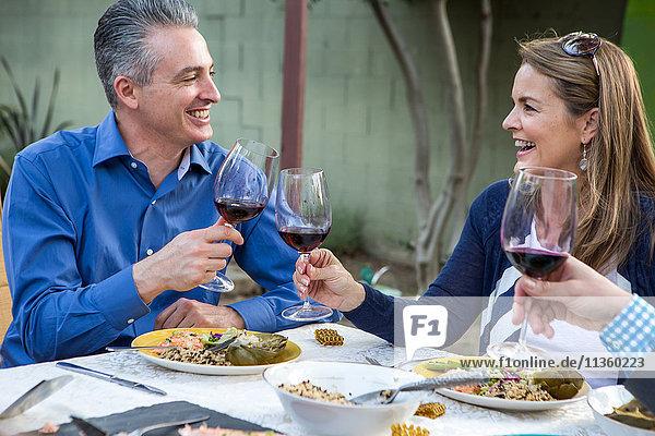 Ältere Freunde stoßen mit Rotwein am Tisch der Gartenparty an