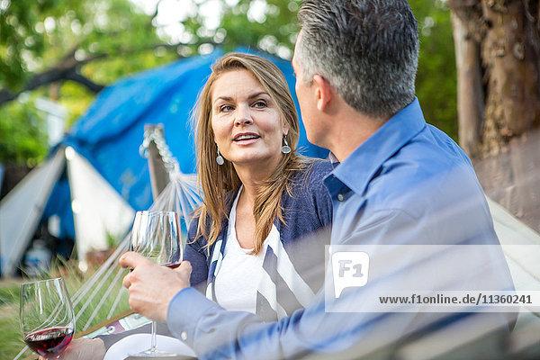 Reifes Paar plaudert auf Hängematte bei Gartenparty
