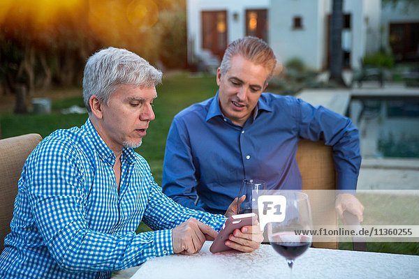 Zwei reife Männer benutzen ein Smartphone am Gartenparty-Tisch