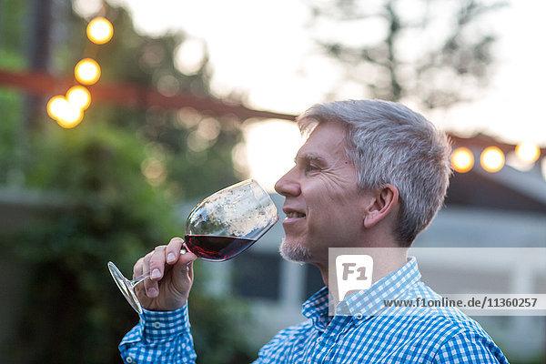 Reifer Mann trinkt Rotwein bei Gartenparty in der Abenddämmerung