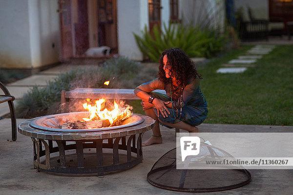Reife Frau kauert in der Abenddämmerung vor dem Feuer im Innenhof