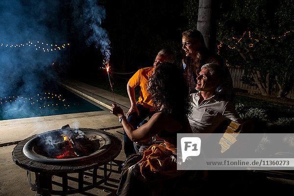 Reife erwachsene Paare  die nachts am Terrassenfeuer Wunderkerzen beobachten