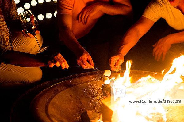 Schnappschuss von reifen erwachsenen Paaren  die nachts auf dem Terrassenfeuer Marshmallows rösten