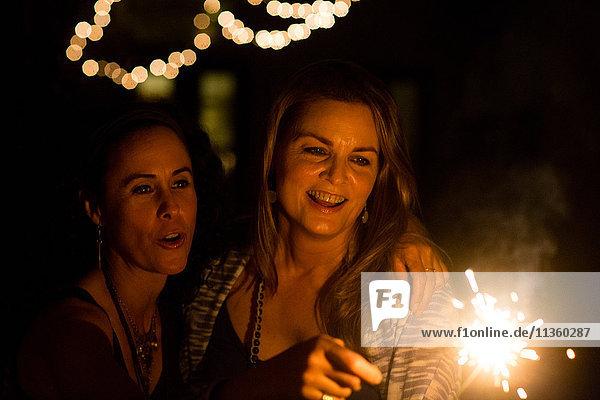 Reife Freundinnen spielen nachts im Garten mit Wunderkerzen