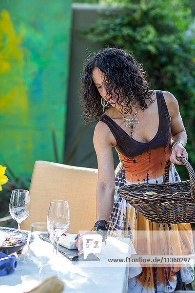 Reife Frau bereitet Gartentisch für Party vor