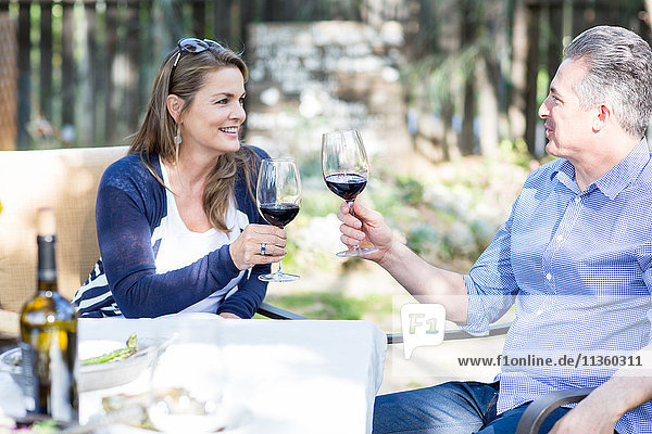 Reifes Paar beim Rotwein-Toast am Gartentisch