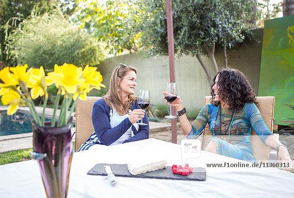 Zwei reife Freundinnen machen einen Rotwein-Toast am Gartentisch