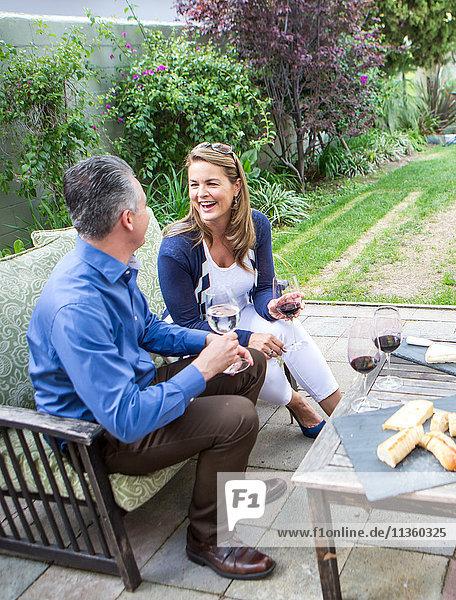 Älteres lachendes Paar auf der Terrasse bei Gartenparty