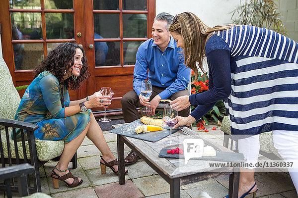 Drei erwachsene Freunde auf der Gartenparty auf der Terrasse