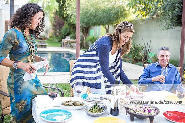 Zwei reife Freundinnen legen Servietten auf den Tisch der Gartenparty