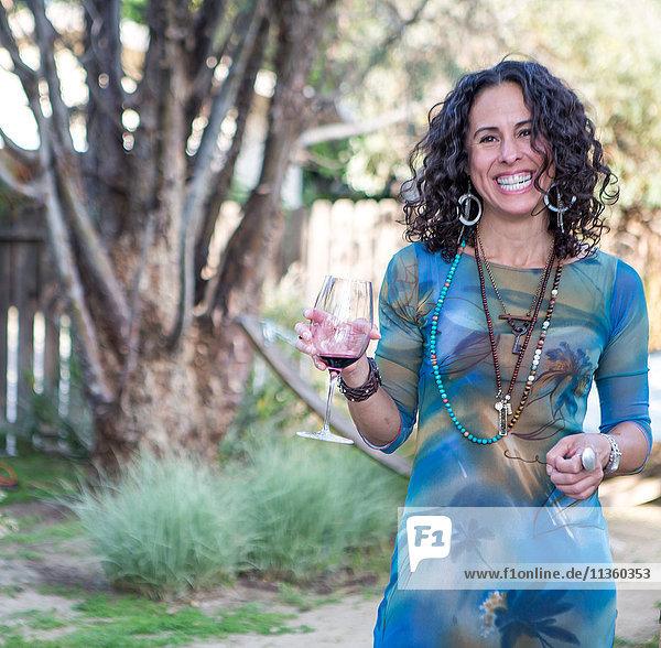 Porträt einer reifen Frau  die auf einer Gartenparty Rotwein hält