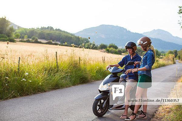 Junge Frau gibt ihrem Freund eine Moped-Fahrstunde auf einer Landstraße  Mallorca  Spanien