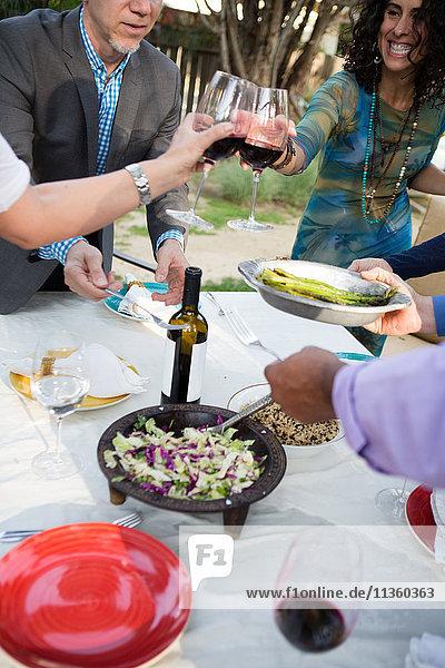 Reife Frauen machen Weintoast am Gartenparty-Tisch