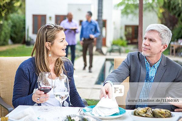 Erwachsener Mann und Frau unterhalten sich am Tisch der Gartenparty