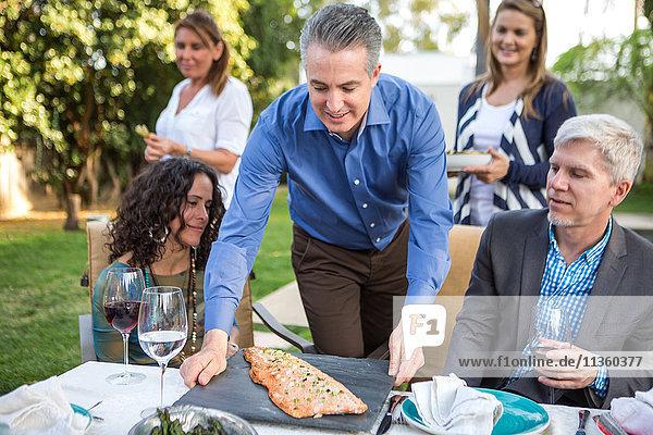Reifer Mann setzt Fischküche auf den Tisch der Gartenparty