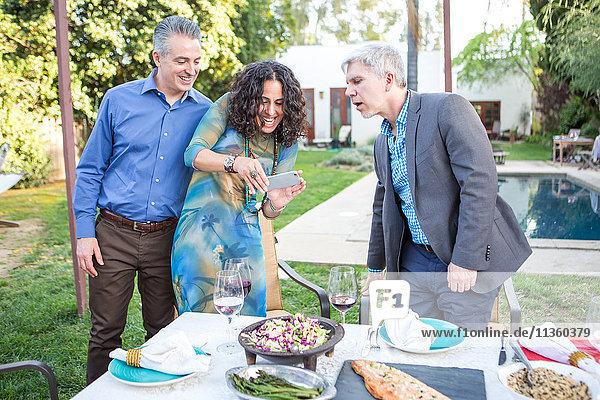Reife Frau fotografiert Gartenparty-Tisch auf Smartphone