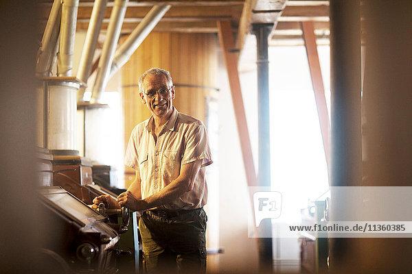 Porträt eines männlichen Müllers  der die Maschine in der Weizenmühle bedient
