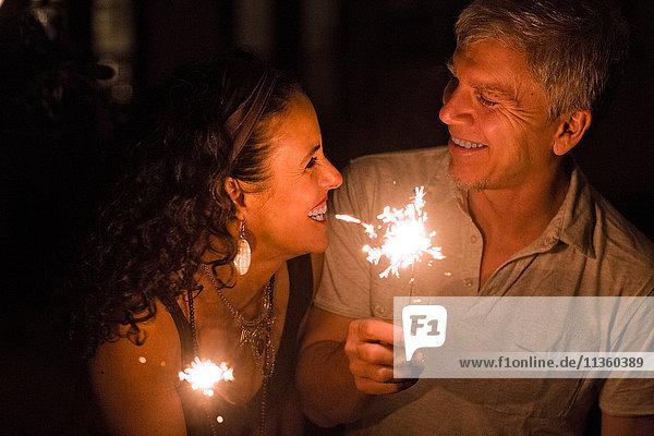 Glückliches  romantisches  reifes Paar hält nachts Wunderkerzen
