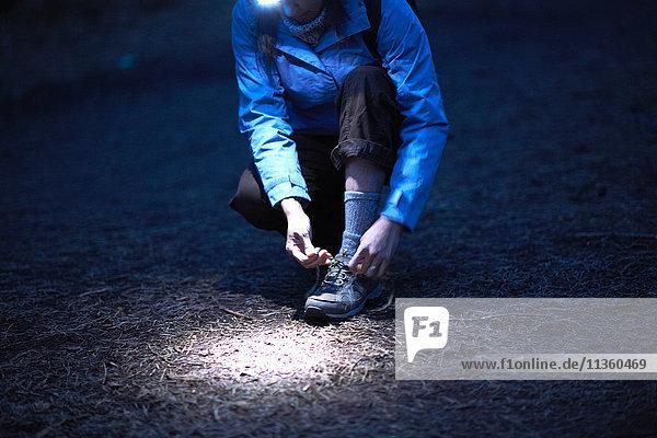 Wanderin mit Stirnlampe beim nächtlichen Schnürsenkelbinden von Wanderschuhen
