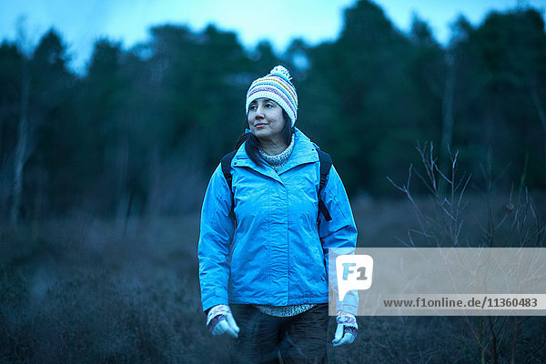 Female hiker hiking in forest at dusk