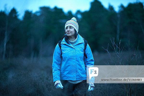 Wanderin wandert in der Dämmerung im Wald