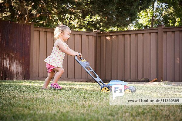 Young girl in garden  pushing toy lawn mower