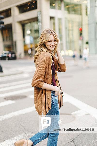 Junge Frau überquert Straße  lächelnd