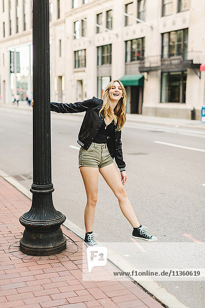 Young woman outdoors  swinging on lamp post  smiling