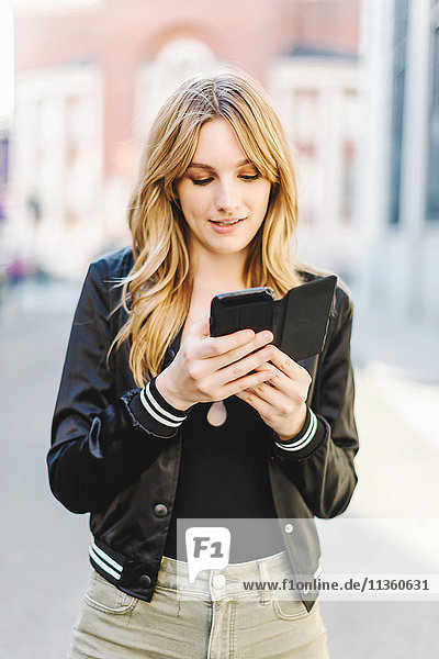 Young woman in street  using smartphone