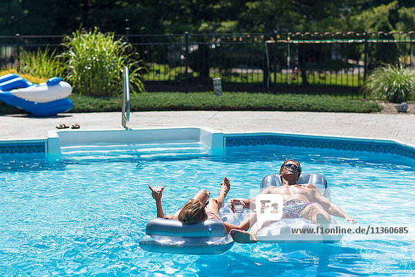 Mature couple in swimming pool  relaxing on inflatables