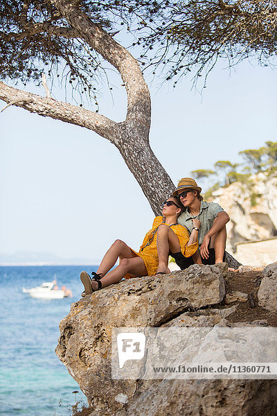 Paar sitzt am Baum und schaut weg  Mallorca  Spanien