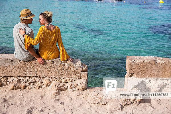 Rückansicht eines auf einer Mauer am Meer sitzenden Paares  Mallorca  Spanien