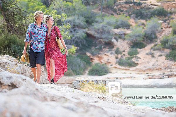 Couple strolling on rocks by sea  Majorca  Spain