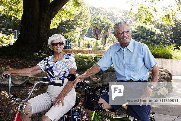 Senior cycling couple on bicycles in park